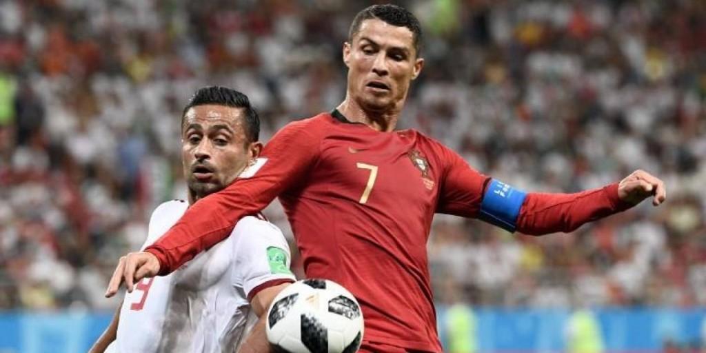 Cristiano Ronaldo pugna por el balón con un jugador iraní